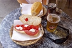 Typical lunch of salami/mozarella/tomato sandwich with cold beer